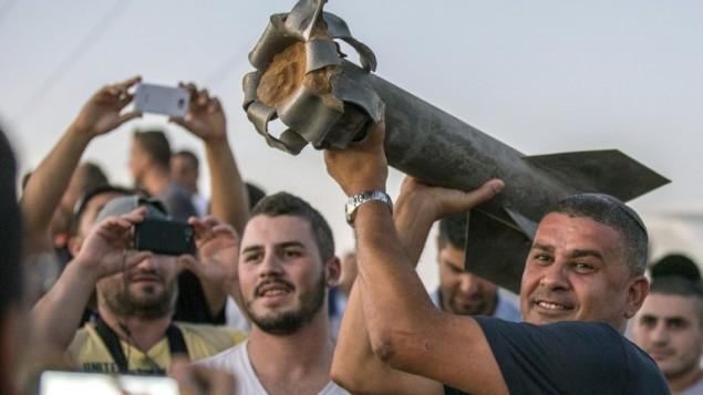 مواطنون اسرائيليون معظمهم من مدينة سديروت في جنوب إسرائيل، يحملون بقايا صاروخ،  13 يوليو عام 2014. AFP PHOTO / JACK GUEZ