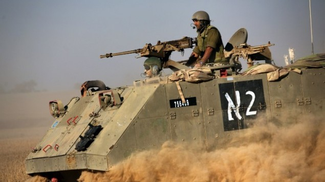 ناقلة جند مدرعة إسرائيلية (APC) تتحرك باتجاه الحدود بين إسرائيل وغزة في منطقة انتشار الجيش  20 يوليو 2014 AFP PHOTO / مناحيم كاهانا