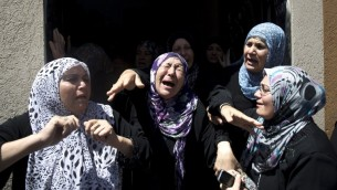 نساء فلسطينيات يبكين  حدادا خلال جنازة حافظ حماد، أحد كبار قادة الجهاد الإسلامي، وخمسة من أفراد عائلته، بينهم امرأتان وطفلان، الذين قتلوا جميعا عندما سقطت قذيفة إسرائيلية في منزلهم في بلدة شمال قطاع غزة بيت حانون في 09 يوليو 2014  AFP PHOTO / MAHMUD HAMS