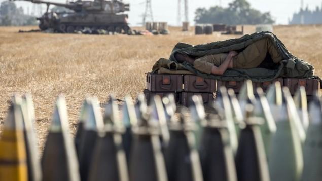 جندي إسرائيلي ينام على صندوق ذخيرة قرب المدفعية 155MMالمتمركزة AFP PHOTO / JACK GUEZ على طول الحدود الإسرائيلية الجنوبية مع قطاع غزة في أعقاب الغارات الجوية الاسرائيلية على قطاع غزة يوم 11 يوليو 2014.