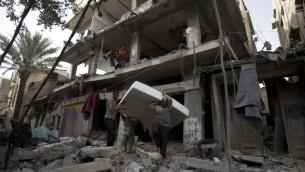 فلسطينيون يحاولون استعادة فراش من تحت أنقاض مبنى مدمر إثر ضربة عسكرية اسرائيلية في مدينة غزة يوم 12 يوليو 2014  AFP PHOTO / MAHMUD HAMS
