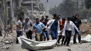 مسعفون يقومون بإخلاء جثة من منطقة الشجاعية شرق غزة  20 يوليو 2014. AFP PHOTO / MAHMUD HAMS