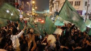 احتفال الفلسطينيين في مدينة رام الله بالضفة الغربية، بعد أن أعلنت كتائب القصام انها أسرت جندي اسرائيلي في وقت متأخر من 21 يوليو 2014 AFP PHOTO / ABBAS MOMANI