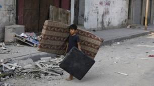 صبي فلسطيني يمشي وسط الحطام في شارع مهجور في وسط مدينة غزة، ويحمل فراش  في محاولة لانقاذ ما تبقى من الشقة المهدومة عائلته22 يوليو 2014.  AFP PHOTO / MOHAMMED ABED