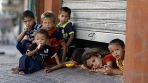 الأطفال الفلسطينيون المنزاحون يطلون من تحت باب مكان تحتمي به أسرهم في مدينة غزة 26 يوليو 2014.  AFP PHOTO / MOHAMMED ABED