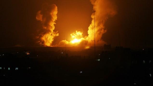 اللهيب يتصاعد من غزة بعد الغارة الجوية الإسرائيلية في رفح، جنوب قطاع غزة، في 1 يوليو 2014. الطائرات الحربية الاسرائيلية شنت في ساعات الصباح الاولى من يوم الثلاثاء، العشرات من الغارات الجوية على أهداف مختلفة في قطاع غزة، بما في ذلك مواقع تابعة لحماس و الجهاد الإسلامي.AFP/ SAID KHATIB