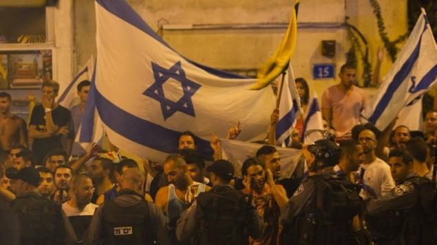 نشطاء اليمين الإسرائيلي يتظاهرون احتجاجا أمام مظاهرة عرب إسرائيل التي تحتج على الهجوم الإسرائيلي على غزة، في مدينة حيفا بشمال اسرائيل يوم 19 يوليو 2014. أ ف ب