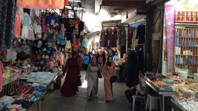 نساء فلسطينيات يمشين خلال حي في البلدة القديمة (الحانان ميلر/ طاقم تايمز أوف إسرائيل)