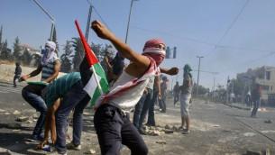 ماثم فلسطيني يرمي الحجارة اثناء اشتباكات مع الشرطة الاسرائيلية في شعفاط بعد مقتل محمد ابو خضير (سليمان خضر/ فلاش ٩٠)