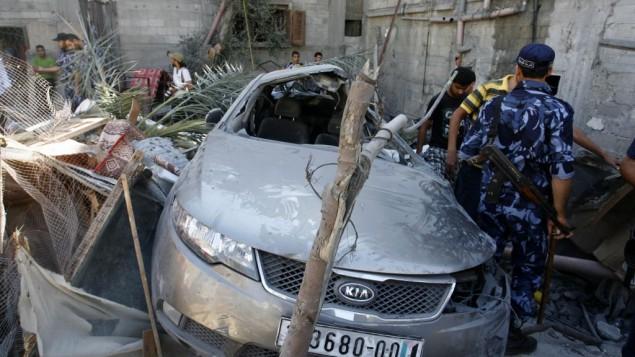 عناصر الامن تتفقد بيت في  موقع سقوط الغارة الاسرائيلية في خان يونس ٨ يوليو ٢٠١٤ غزة (عبد الرحيم خطيب/ فلاش ٩٠)