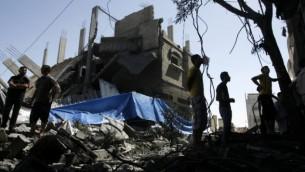فلسطينيون يقفون بين انقاض بيت دمر بعد غارة اسرائيلية على رفح ١٤ يوليو ٢٠١٤ (فلاش ٩٠)