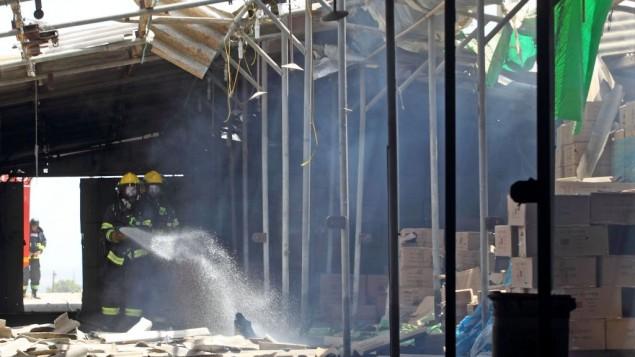 عناصر الانقاذ والاطفاء في ساحة سقوط صاروخ من غزة على بيت في كبوتس نير عام  (فلاش ٩٠)