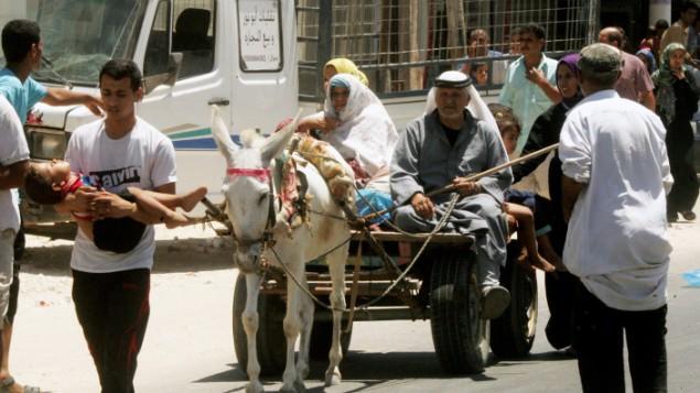 عائلات فلسطينية المنزاحة في طريقهم بحثا عن مكان أكثر أمنابينما يواصل الجيش الاسرائيلي  قصف منطقة خان يونس، في جنوب قطاع غزة  24 يوليو 2014Abed Rahim Khatib/Flash90