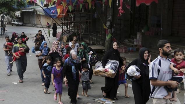 فلسطينيون يتركون بيوتهم في حي الشجاعية بعد القصف الإسرائيلي الثقيل 20 يوليو 2014 AFP PHOTO