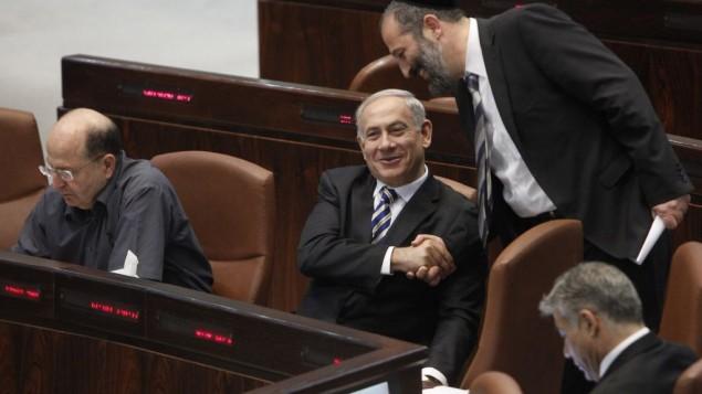 رئيس الوزراء بنيامين نتنياهو يصافح رئيس حزب شاس المتدين خلال جلسة في الكنيست يونيو 2013 (مريام الستير/ فلاتش 90)