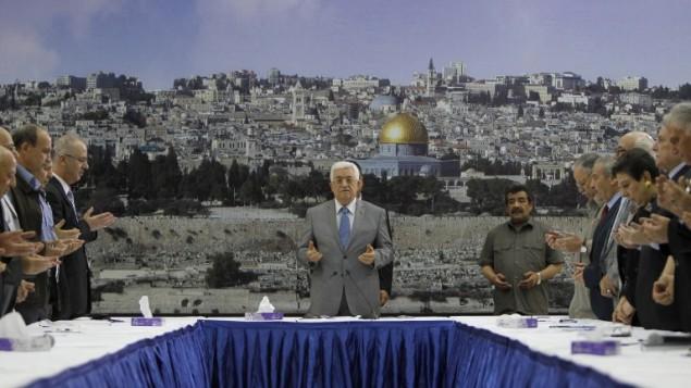 رئيس السلطة الفلسطينية محمود عباس يقرأ الفاتحة في بداية جلسة الحكومة 9 يوليو 2014 (أ ف ب/ عباس مومني)