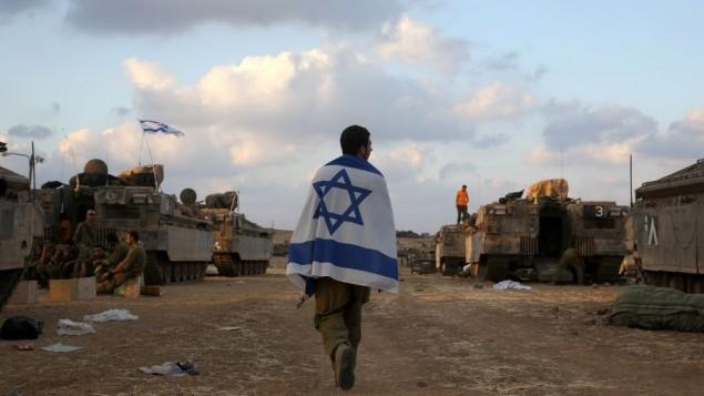 جندي اسرائيلي يلف نفسه بالعلم الاسرائيلي عند الحدود مع غزة 19 يوليو 2014 (ناتي شوحاط/ فلاش 90)