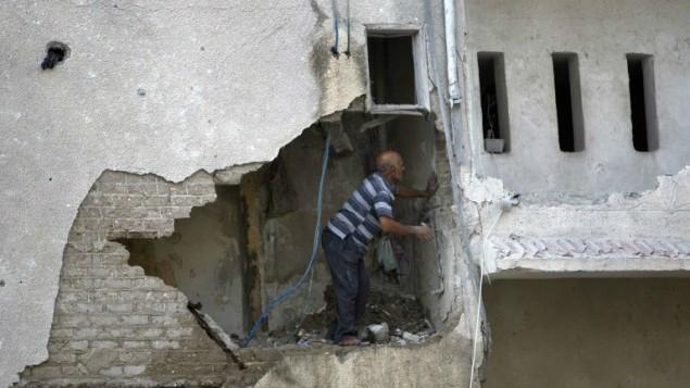 رجل فلسطيني يتفحص الاضرار لبيت هدم جزئيا جراء غارة اسرائيلية 19 يوليو 2014 (أ ف ب)