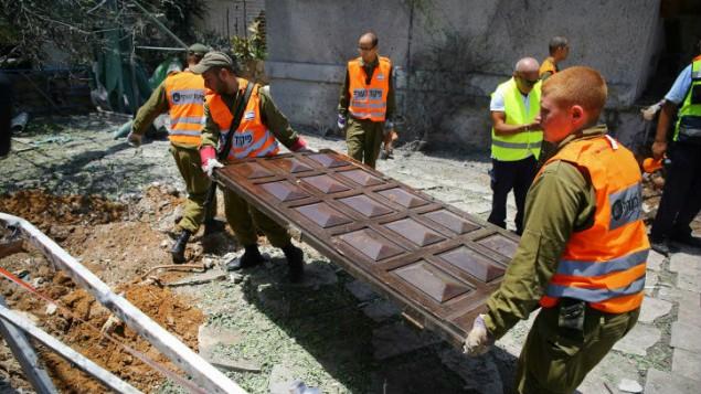 عناصر الانقاذ والاطفاء في ساحة سقوط صاروخ من غزة على بيت في مدينة اشدود الاسراءيلية (فلاش ٩٠)