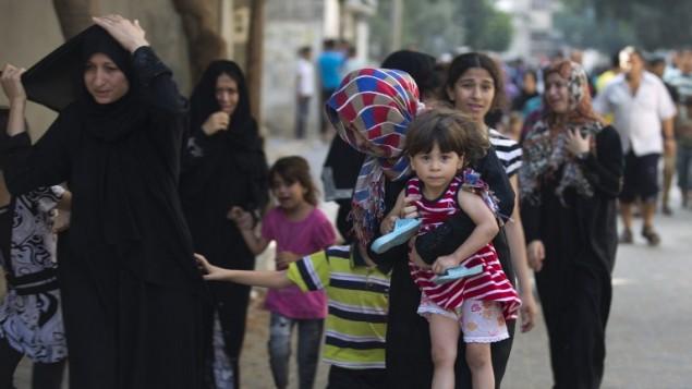 عائلات فلسطسنية تترك بيوتها بعد غارات اسرائيلية ليلية على مدينة غزة 10 يوليو 2014 (محمد عبد/ أ ف ب)