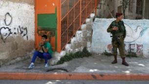 صبي فلسطيني يجلس بالقرب من الجنود الاسرائيليين المنتشرين في مدينة الخليل بالضفة الغربية، في أول جمعة من شهر رمضان  Nati Shohat/FLASH90
