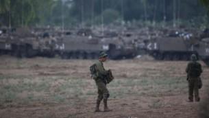 """جندي يقف في سهل قرب الحدود مع غزة, في الافق تقف """"ناقلات جنود مدرعة"""" 9 يوليو 2014 (يوناتان سنايدل/ فلاش 90)"""