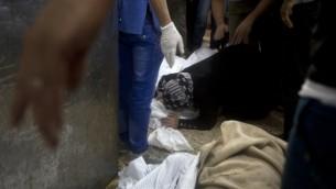 امرأة  تبكي فوق جثة على الارض في مستشفى الشفاء في غزة 20 يوليو 2014 (أ ف ب)