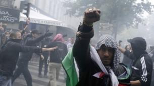 متظاهر يرتدي الكوفية والعلم الفلسطيني  13 يوليو 2014 في باريس، خلال مظاهرة ضد اسرائيل ودعما للسكان في قطاع غزة.  AFP/KENZO TRIBOUILLARD