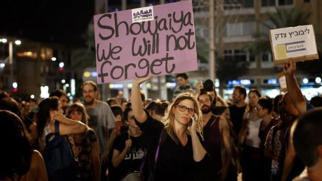 """ناشطة سياسية يسارية ترفع لافتة مكتوب عليها """"الشجاعية لن تنسى"""" في ساحة رابين, تل ابيب 26 يوليو 2014  Thomas Coex/AFP"""
