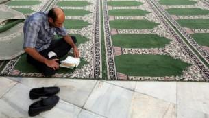 رجل مسلم يقرأ القرأن خلال شهر رمضان 2 يوليو 2014 (عطا قيناوي/ أ ف ب)