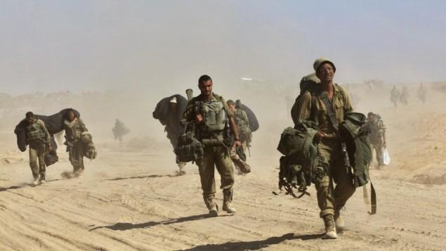 جنود المشاة الإسرائيليين  بالقرب من الحدود بين اسرائيل وقطاع غزة بعد عودتهم من القطاع الساحلي الفلسطيني الذي تسيطر عليه حماس  4 أغسطس 2014   AFP PHOTO/GIL COHEN-MAGEN