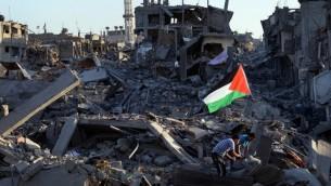 سكان بين أنقاض منزلهم المحطمة ، وعلم الفلسطيني وسط لادمار، في حي الشجاعية في مدينة غزة 7 أغسطس 2014. AFP PHOTO / ROBERTO SCHMIDT