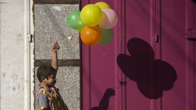 صبي فلسطيني يلعب مع بالونات ا في حي الشجاعية مدينة غزة  خوفا من الهجمات الإسرائيلية، بعد أن رفضت الفصائل الفلسطينية في غزة تمديد وقف إطلاق النار لمدة 72 ساعة . 8 آب، 2014. AFP PHOTO / MAHMUD HAMS