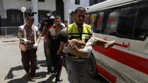 موظف الطوارئ يحمل الطفل الذي أصيب بجروح في غارة جوية إسرائيلية على حي الشيخ رضوان شمال مدينة غزة،  مستشفى الشفاء في المدينة،  8 أغسطس 2014.  AFP PHOTO / MOHAMMED ABED