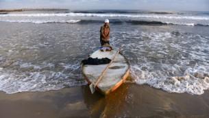 ياسر السلطان،  صياد فلسطيني يسحب قاربه على الأمواج قبالة الشاطئ  10 أغسطس عام 2014 في مدينة غزة. الصيادون يتفقون على أن هناك أقل وأقل اسماك  بسبب مياه الصرف الصحي التي تلقى في المحيط والتي تقود الأسماك أبعد إلى داخل البحر. AFP PHOTO / ROBERTO SCHMIDT