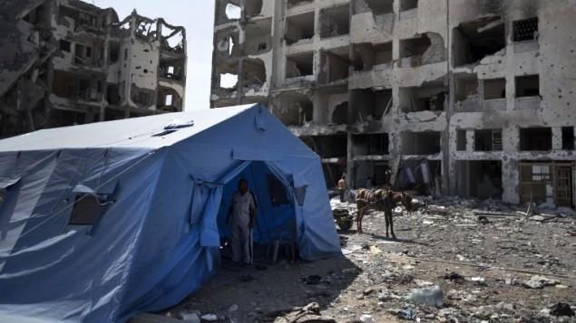 11 أغسطس عام 2014 في بيت لاهيا في شمال قطاع غزة , خيمة نصبت أمام أبراج دمرت خلال وقف إطلاق النار لمدة 72 ساعة  AFP PHOTO / MAHMUD HAMS