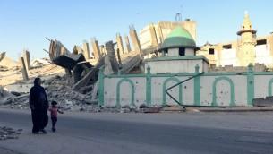 امرأة فلسطينية وطفل يمشيان بجانب المسجد العمري الذي دمر في 12 أغسطس  2014 في جباليا، شمال قطاع غزة. مزق صاروخ اسرائيلي خلال سقف مقبب  من الحجر الرملي. دمرت إصابة مباشرة المسجد العمري في جباليا. ويعتقد الموقع أن يضم مسجدا بني في القرن السابع وأجزاء منه تعود إلى القرن الرابع عشر AFP PHOTO/ROBERTO SCHMIDT