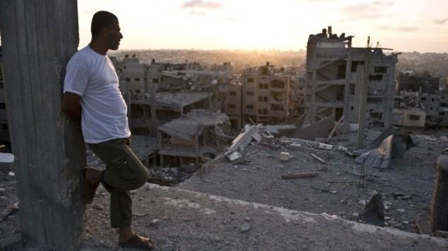 رجل امام أنقاض مبان سكنية دمرت خلال القتال بين نشطاء حماس وإسرائيل في في شمال قطاع غزة،  16 أغسطس 2014. AFP PHOTO / ROBERTO SCHMIDT
