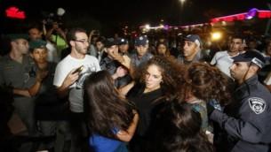 ناشطو المنظمة اليمينية لمنع الاستيعاب في الأراضي المقدسة (LEHAVA) اثناء اشتباكات مع الشرطة خلال مظاهرة خارج قاعة الزفاف حيث تزوج محمود منصور، العربي الإسرائيلي، من موريل مالكا، اليهودية الاصل، أغسطس 17،  2014 في ريشون لتسيون. AFP/GALI TIBBON