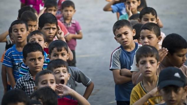 أطفال فلسطينيون  في ساحة مدرسة للأمم المتحدة، خلال النشاط الصباحي وكان من المفترض أن تبدأ الدراسة في مدينة غزة  24 أغسطس 2014. AFP PHOTO / ROBERTO SCHMIDT