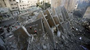 سكان فلسطينيون وعناصر الاسعاف يتفقدون بقايا المبنى الذي دمرته الغارات الاسرائيلية والتي اسفرت عن مقتل 2 واصابة 20, مدينة غزة 26 اغسطس 2014 AFP PHOTO/MAHMUD HAMS