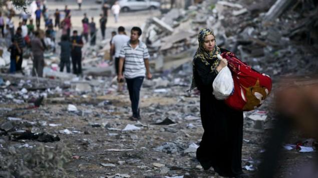 امرأة فلسطينية نازحة تأخذ بعض أمتعتها من منزلها  26 أغسطس 2014AFP/ROBERTO SCHMIDT