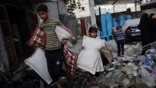 فلسطينيون من غزة ينقذون ما يستطيعون من بقايا منازلهم التي دمرتها غارة جوية اسرائيلية على مدينة رفح في جنوب قطاع غزة  26 أغسطس  2014. AFP PHOTO/ SAID KHATIB