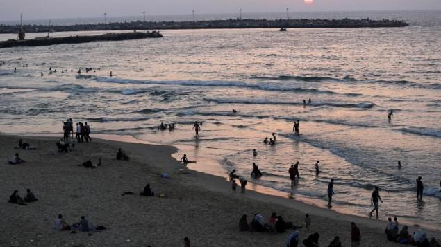 عائلات فلسطينية على الشاطئ في مدينة غزة أثناء غروب الشمس  27 أغسطس 2014 بعد الموافقة على هدنة طويلة الأجل. AFP PHOTO / MOHAMMED ABED
