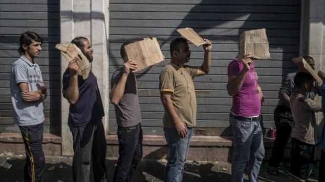 رجال فلسطينيون يحملون قطعة من الورق المقوى لحماية أنفسهم من الشمس عند وقوفهم في صف للحصول على الخبز في شارع بوسط مدينة غزة  30 يوليو 2014. AFP PHOTO / MARCO LONGARI