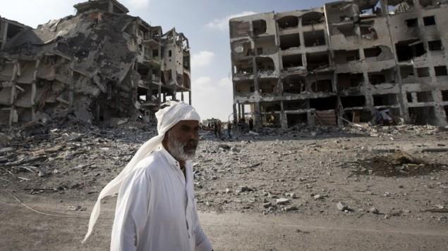 رجل فلسطيني في غزة يسير امام عمارات مهدمة 5 اغسطس، غزة ( AFP/ MAHMUD HAMS)