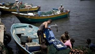 صيادون فلسطينيون يفرغون صيدهم في ميناء مدينة غزة 5 أغسطس 2014، وبعد دخول هدنة لمدة 72 ساعة وافقت عليها إسرائيل وحماس حيز التنفيذ . AFP PHOTO / MAHMUD HAMS
