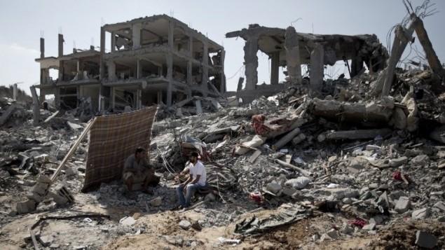 رجال فلسطينيون يتفقدون الدمار حول بيوتهم خلال الهدنة  في حي التفاح, غزة. 6 اغسطس 2014  AFP PHOTO / MAHMUD HAMS