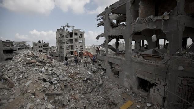 فلسطينيون بين انقاض المباني المدمرة في جزء من حي التفاح، مدينة غزة اثناء  وقف إطلاق النار  6 أغسطس 2014.  AFP PHOTO / MAHMUD HAMS