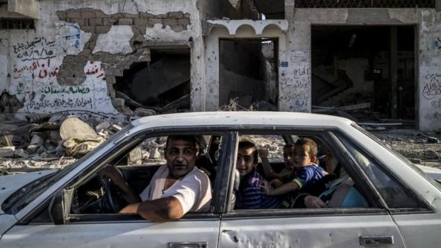أسرة فلسطينية تسوق عبر حارة مهدمة امام مبنى مدمر في حي الشجاعية  مدينة غزة 6 أغسطس 2014.  AFP PHOTO / MARCO LONGARI